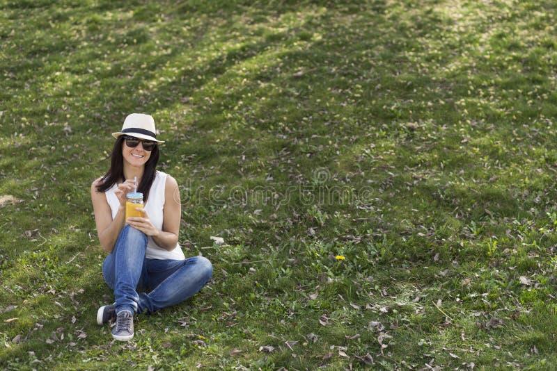 Jovem mulher bonita que aprecia um suco de laranja em um parque É imagens de stock royalty free
