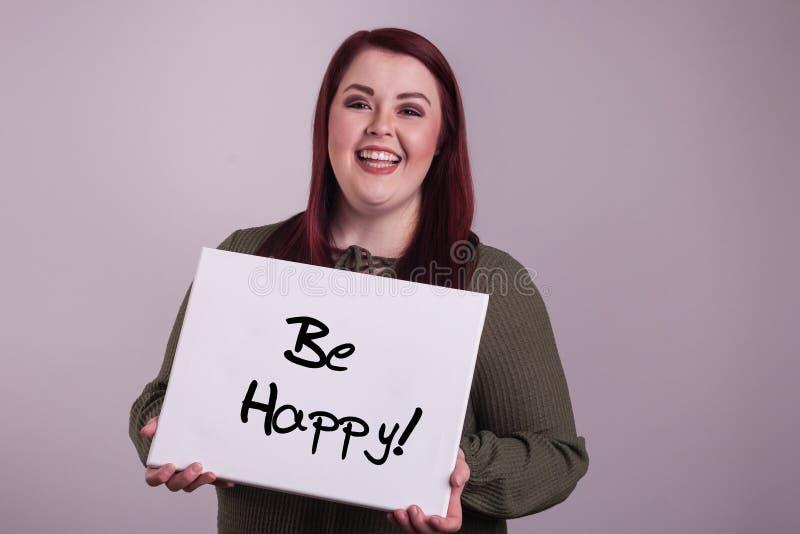 A jovem mulher bonita que apresenta um sinal que diga esteja feliz pintada no whiteboard imagem de stock royalty free