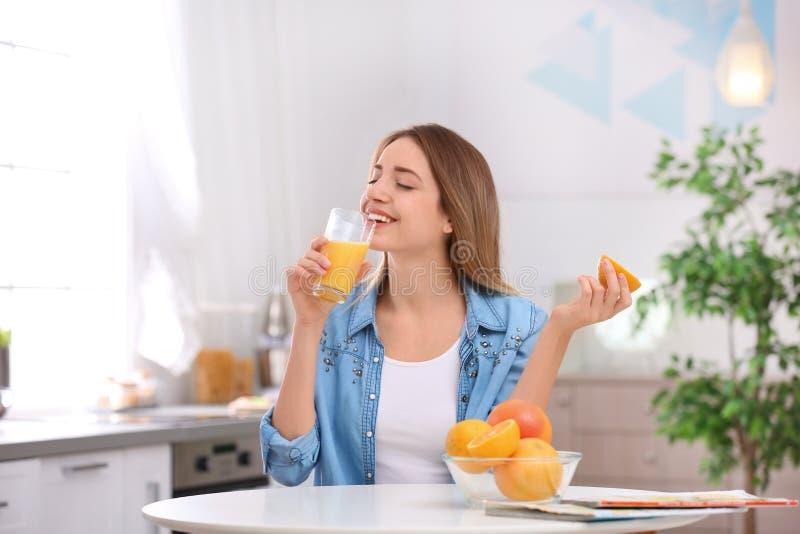 Jovem mulher bonita que bebe o suco de laranja fresco na cozinha imagens de stock