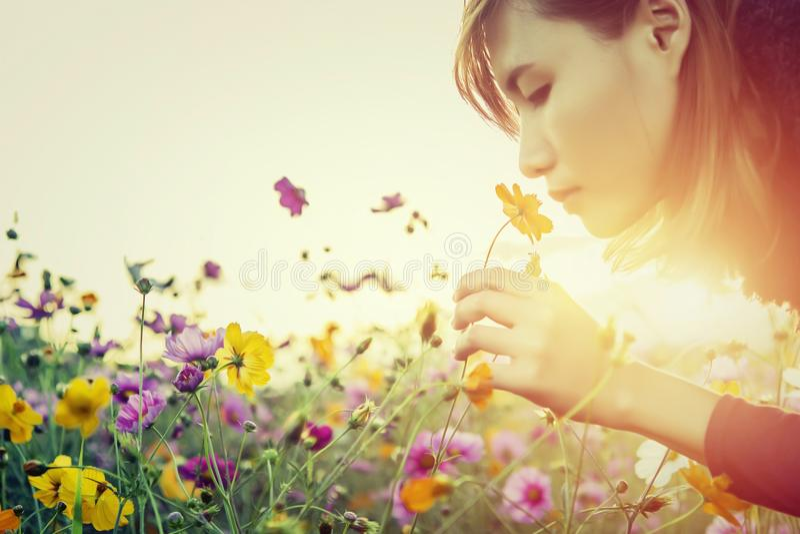 Jovem mulher bonita que cheira as flores foto de stock royalty free