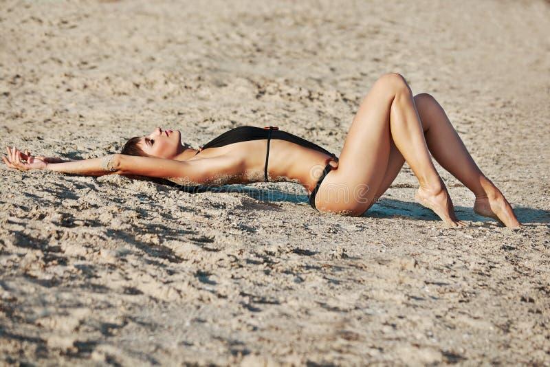 Jovem mulher bonita que coloca na costa de mar imagem de stock royalty free