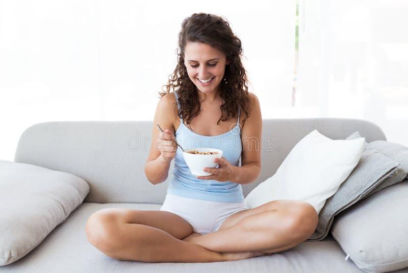 Jovem mulher bonita que come cereais em casa imagem de stock