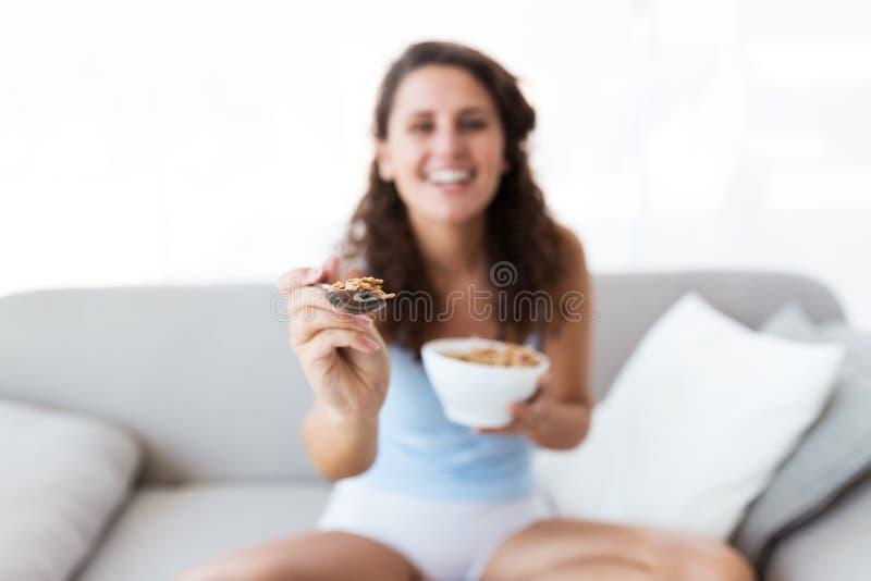 Jovem mulher bonita que come cereais em casa fotografia de stock