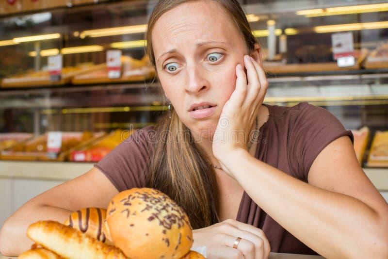 Jovem mulher bonita que come doces no café Hábitos maus saúde foto de stock royalty free