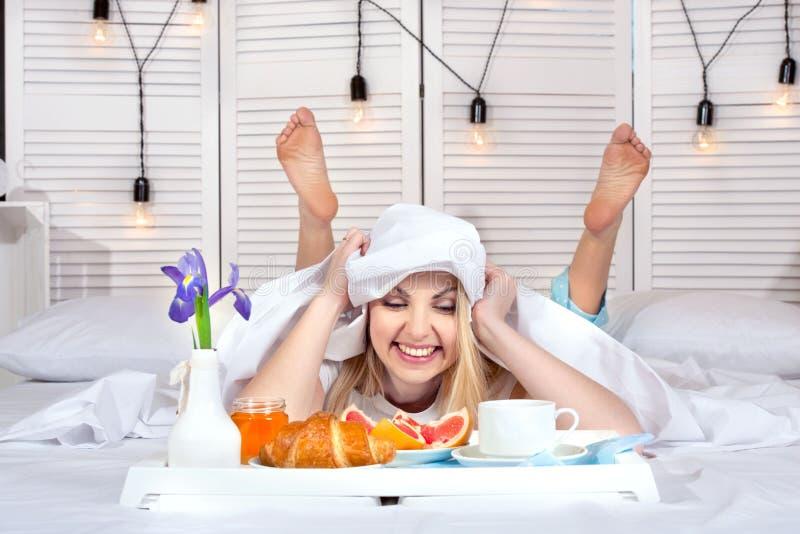 Jovem mulher bonita que come o café da manhã na cama Surpresa do marido amado Comemorando o dia de uma mulher, o dia de mãe fotografia de stock royalty free