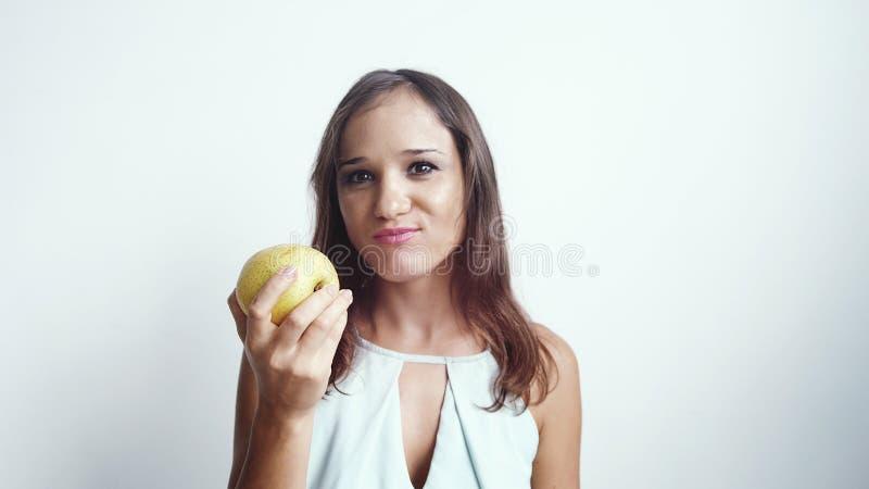 Jovem mulher bonita que come o fruto verde da maçã Isolado no fundo branco fotografia de stock
