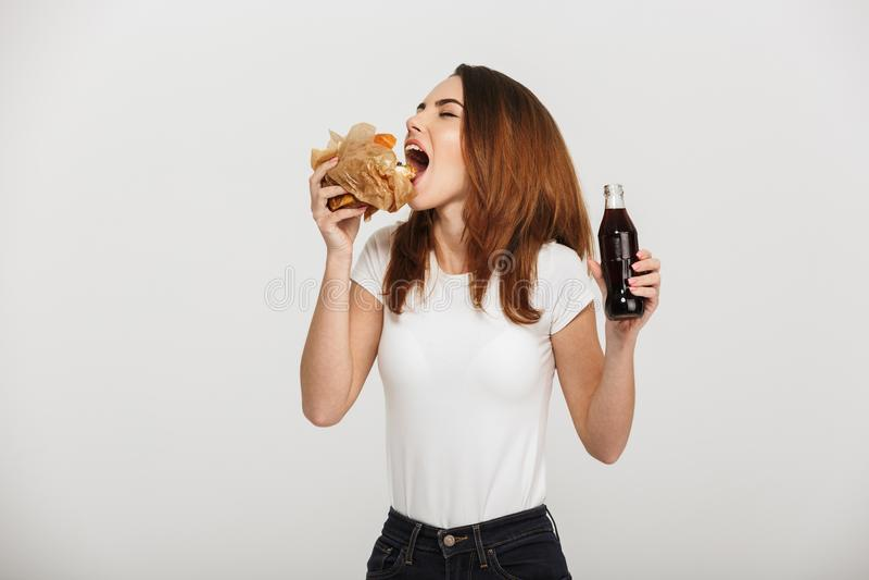 Jovem mulher bonita que come a soda bebendo do hamburguer foto de stock royalty free