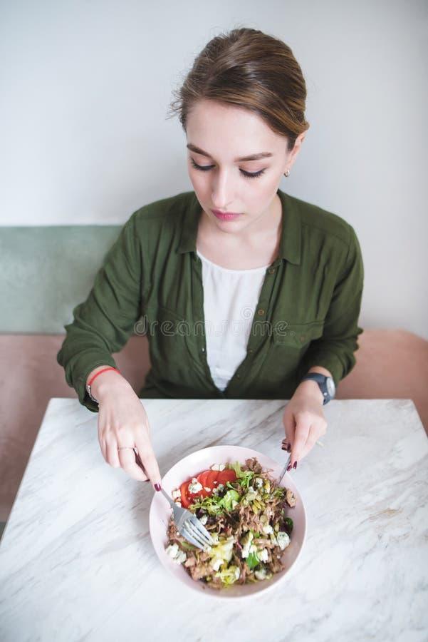 jovem mulher bonita que come uma salada apetitosa em um restaurante com um interior claro fotografia de stock royalty free