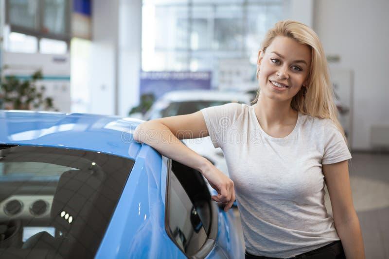 Jovem mulher bonita que compra o carro novo no negócio fotografia de stock royalty free