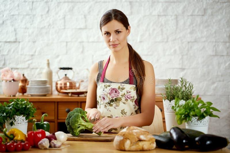 Jovem mulher bonita que corta brócolis na cozinha em uma tabela completamente dos vegetais imagens de stock