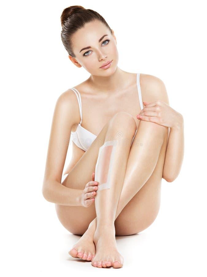 Jovem mulher bonita que depila os pés encerando foto de stock