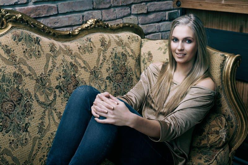 Jovem mulher bonita que descansa em casa no sofá fotografia de stock