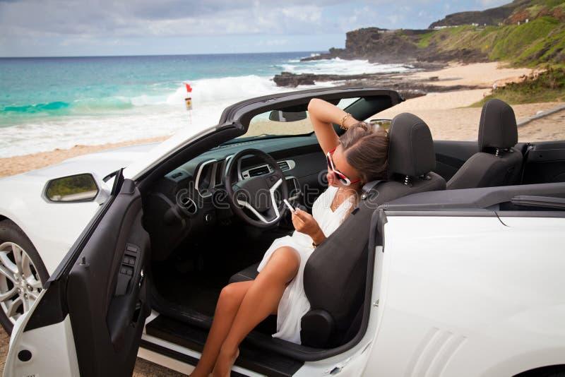 Jovem mulher bonita que descansa em seu carro imagens de stock royalty free