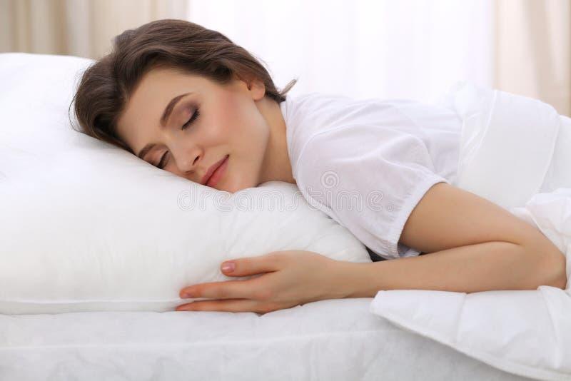 Jovem mulher bonita que dorme ao encontrar-se em sua cama Conceito do restabelecimento agradável e do resto para a vida ativa foto de stock royalty free