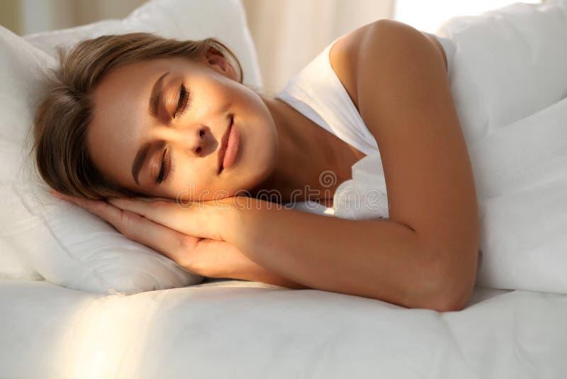 Jovem mulher bonita que dorme ao encontrar-se na cama confortavelmente e alegremente Alvorecer do raio de sol em sua cara foto de stock royalty free