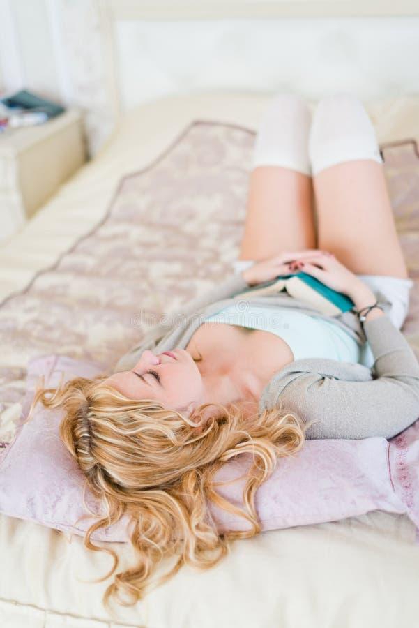 Jovem mulher bonita que dorme com livro imagem de stock royalty free