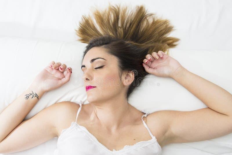 Jovem mulher bonita que dorme em uma cama branca com o tatoo do pássaro imagem de stock royalty free