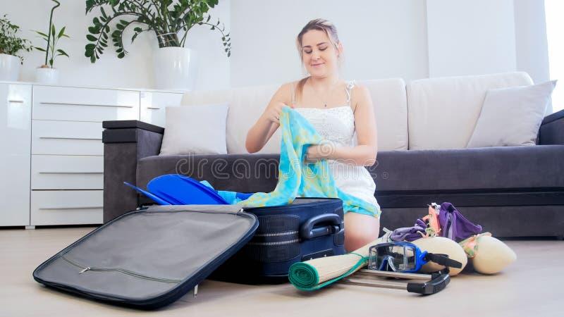 Jovem mulher bonita que embala sua mala de viagem para férias da praia do verão foto de stock royalty free