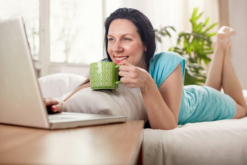 Jovem mulher bonita que encontra-se na cama com xícara de café imagens de stock