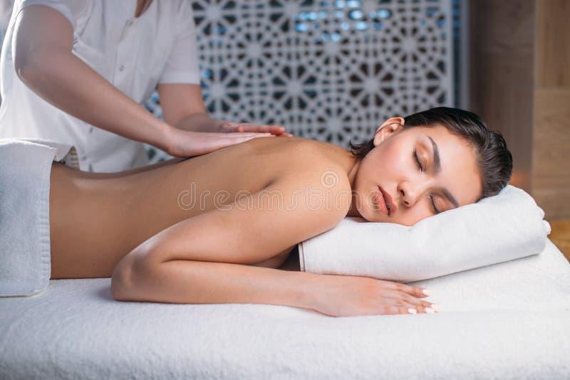 Jovem mulher bonita que encontra-se na cama quando massagista que faz massagens a para trás foto de stock royalty free