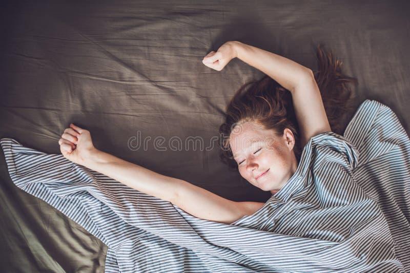 Jovem mulher bonita que encontra-se para baixo na cama e que dorme, vista superior Não obtenha bastante conceito do sono foto de stock