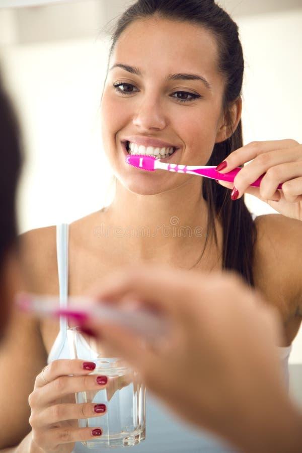 Jovem mulher bonita que escova seus dentes no banheiro foto de stock