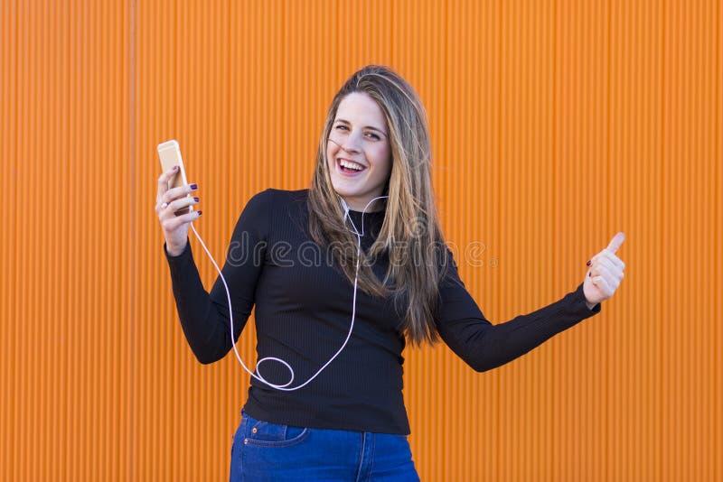 Jovem mulher bonita que escuta a música com fones de ouvido e havi fotografia de stock