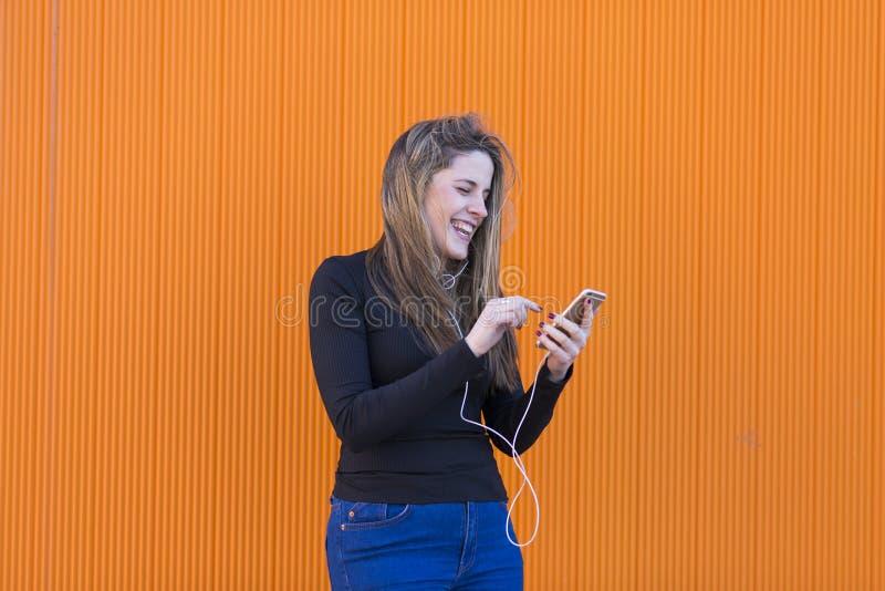 Jovem mulher bonita que escuta a música com fones de ouvido e havi foto de stock