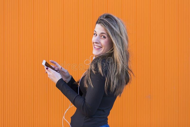 Jovem mulher bonita que escuta a música com fones de ouvido e havi fotos de stock
