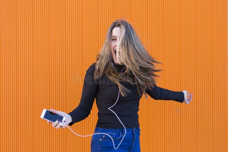 Jovem mulher bonita que escuta a música com fones de ouvido e havi fotografia de stock royalty free