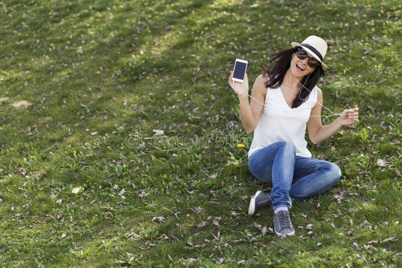 Jovem mulher bonita que escuta a música em seu telefone esperto ela fotos de stock