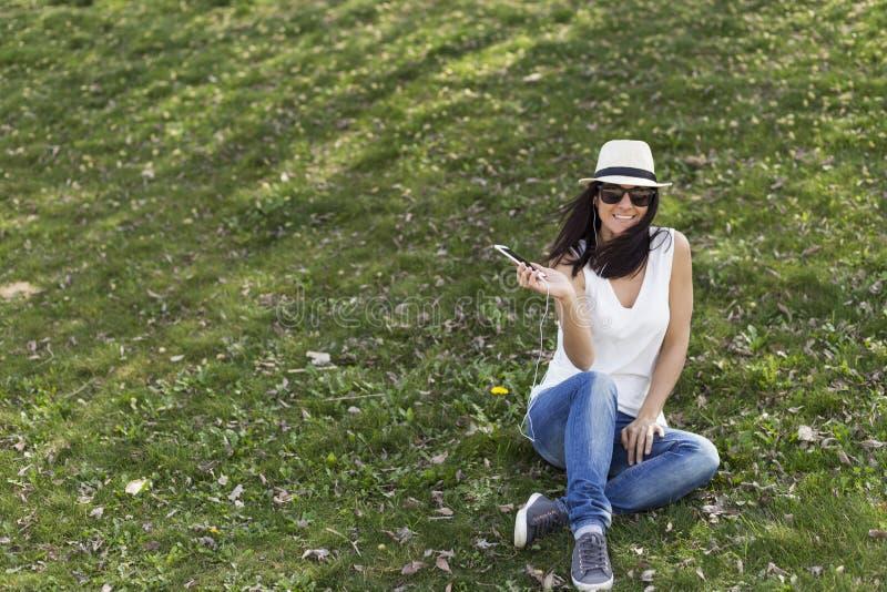 Jovem mulher bonita que escuta a música em seu telefone esperto ela fotografia de stock