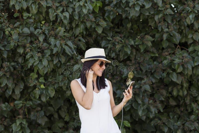 Jovem mulher bonita que escuta a música em seu telefone esperto ela foto de stock