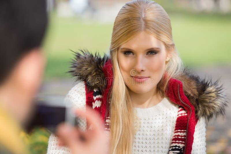 Jovem mulher bonita que está sendo fotografada pelo homem no parque foto de stock
