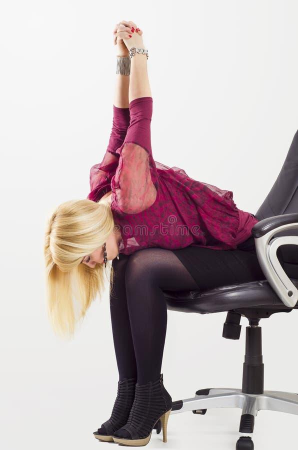Jovem mulher bonita que estica os braços na cadeira do escritório foto de stock