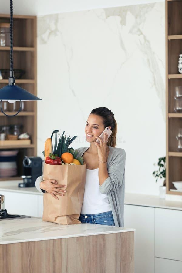 Jovem mulher bonita que fala em seu telefone celular ao guardar o saco de compras com os legumes frescos na cozinha imagens de stock