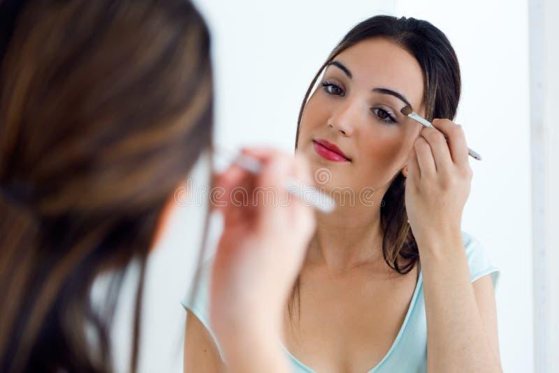 Jovem mulher bonita que faz a composição perto do espelho imagens de stock