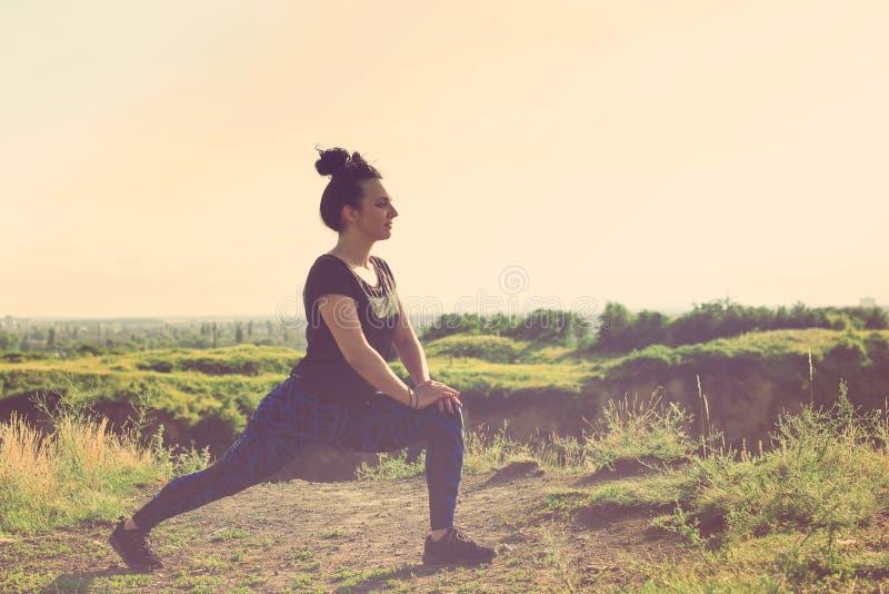 A jovem mulher bonita que faz exercícios no monte sobre a cidade, ostenta fora fotografia de stock royalty free