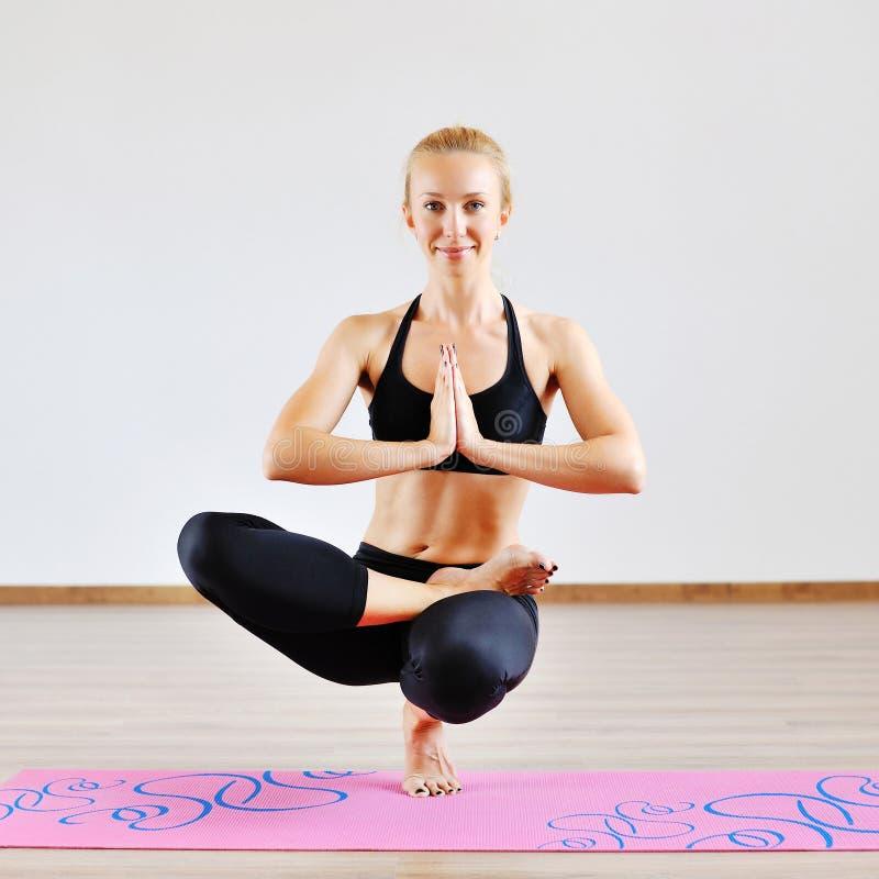 Jovem mulher bonita que faz a ioga em uma posição do pé imagens de stock
