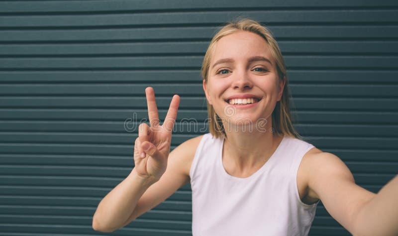Jovem mulher bonita que faz o autorretrato em um smartphone em um fundo da parede fotos de stock royalty free