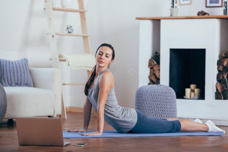 Jovem mulher bonita que faz o exercício em casa imagem de stock