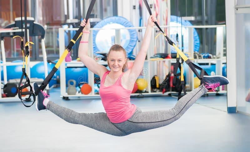 Jovem mulher bonita que faz o exercício em TRX fotos de stock royalty free