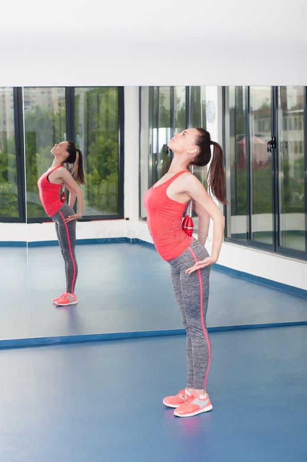 Jovem mulher bonita que faz o gimnastics no assoalho com macis foto de stock