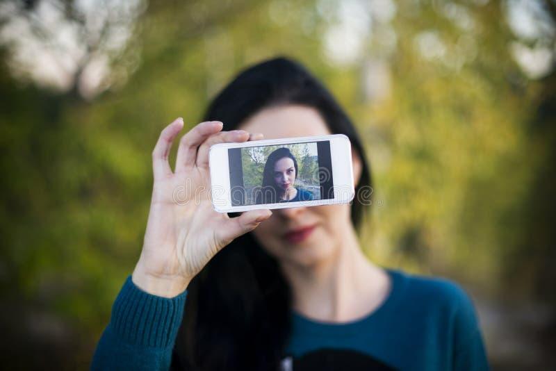 Jovem mulher bonita que faz o selfie fora fotos de stock royalty free