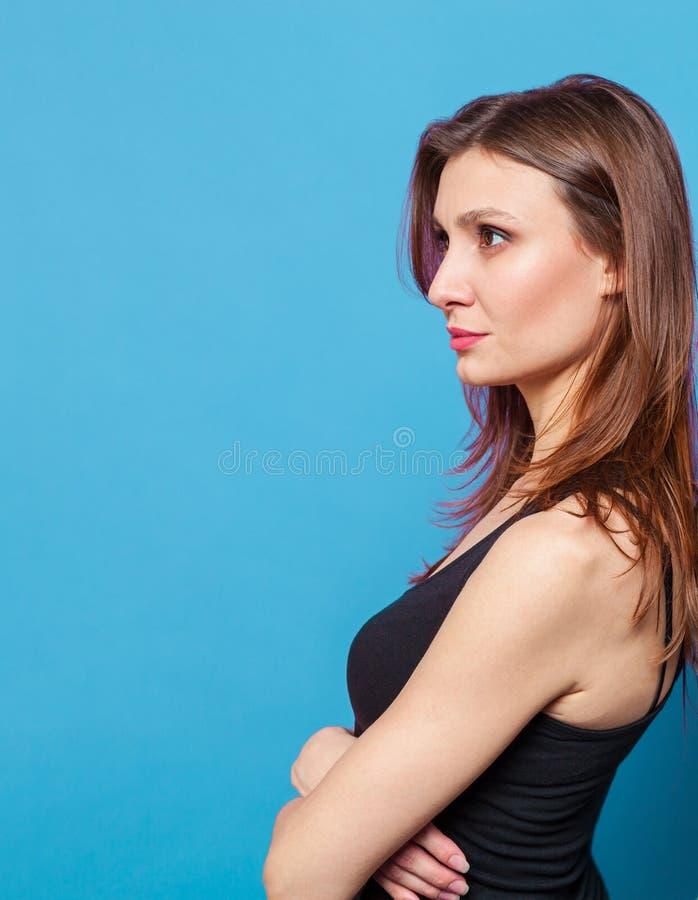 A jovem mulher bonita que fica de volta à parede com mãos cruzou-se fotografia de stock