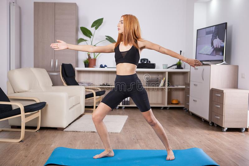 Jovem mulher bonita que fica na pose da ioga do guerreiro II foto de stock