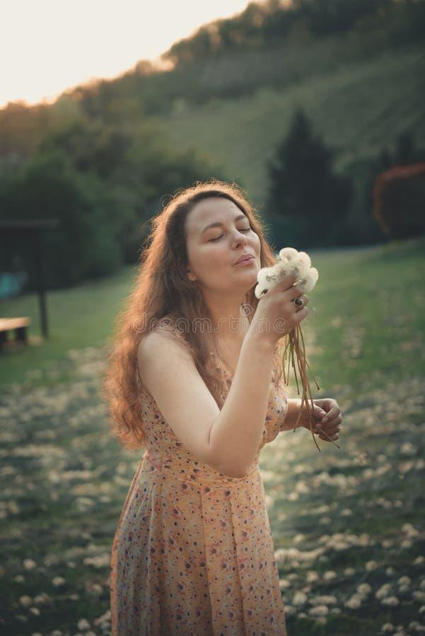 Jovem mulher bonita que funde um dente-de-leão imagens de stock