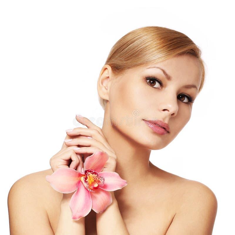 Jovem mulher bonita que guarda a flor da orquídea, isolada foto de stock royalty free