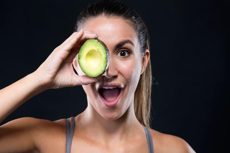 Jovem mulher bonita que guarda o abacate sobre o fundo preto fotografia de stock