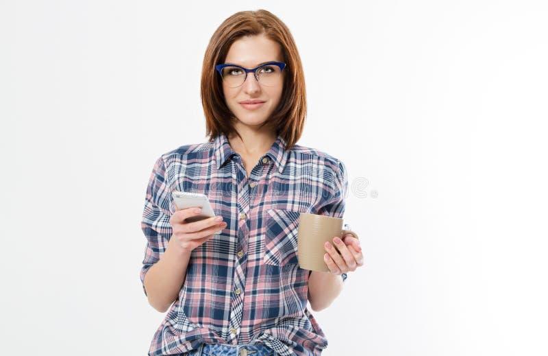 Jovem mulher bonita que guarda o telefone esperto, usando o dispositivo, vidros à moda vestindo, sorrindo, isolado no fundo branc imagens de stock